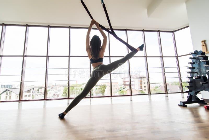 做重力飞行瑜伽asana伸展运动的适合年轻女人在健身训练白色健身房演播室 操作体育健康的生活方式 免版税图库摄影