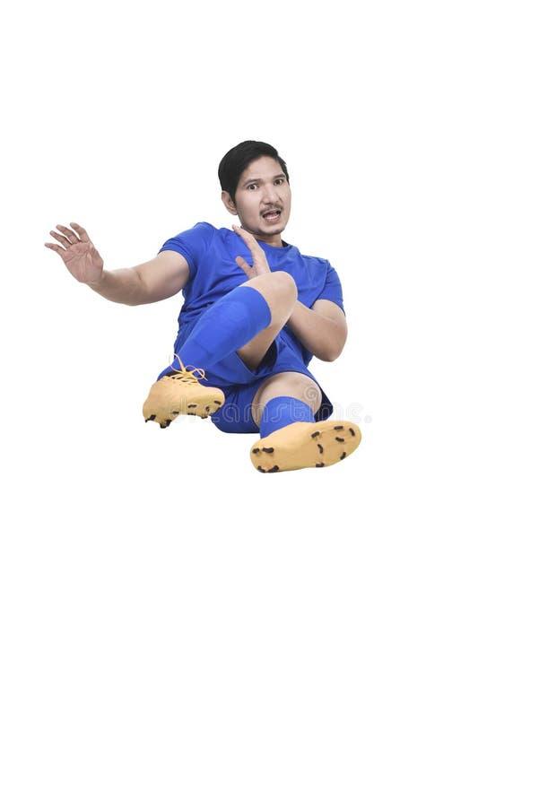 做铲球的亚裔男性足球运动员的图象 库存照片