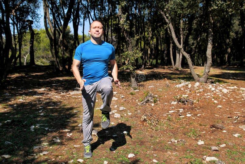 做锻炼在森林英俊的运动员佩带的运动服的人跑的到位锻炼跑到位锻炼 图库摄影