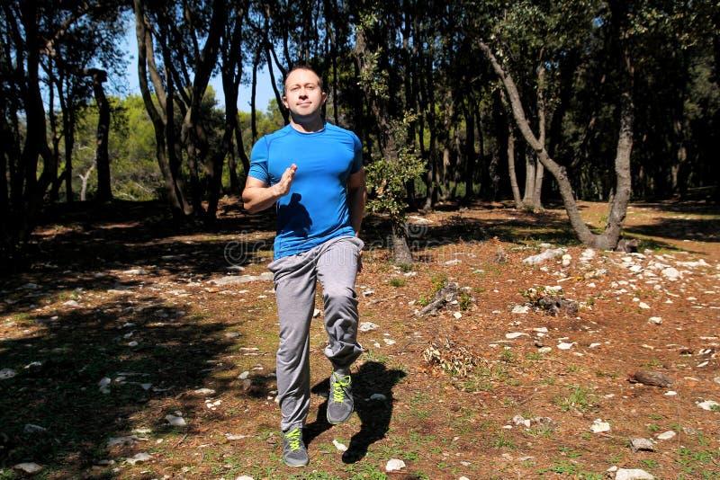 做锻炼在森林英俊的运动员佩带的运动服的肌肉的人跑的到位锻炼跑到位锻炼 免版税库存图片
