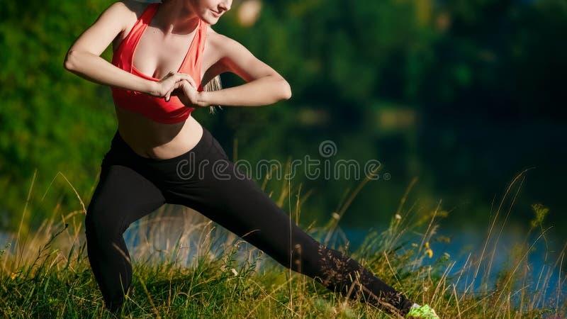 做锻炼本质上的年轻白肤金发的妇女 一件红色背心的体育女孩在公园站立在河附近 免版税库存照片