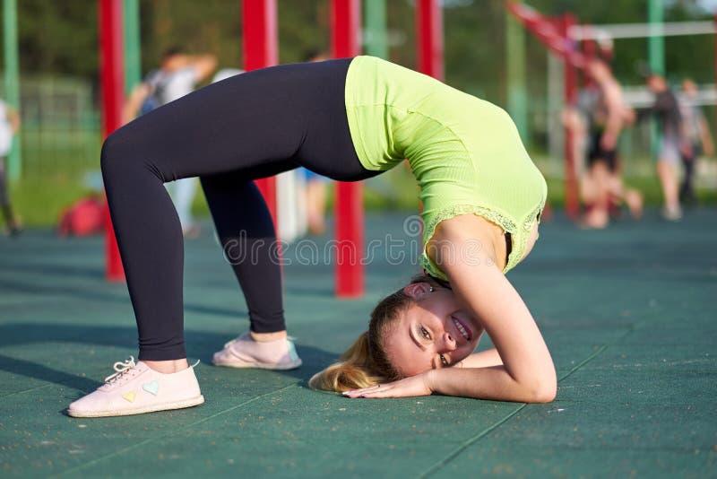 做锻炼桥梁的妇女 舒展danser或体操运动员在锻炼运动场的训练火车 库存图片