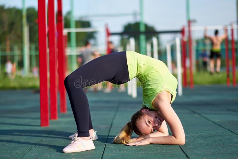 做锻炼桥梁的妇女 舒展danser或体操运动员训练在锻炼运动场训练 库存图片