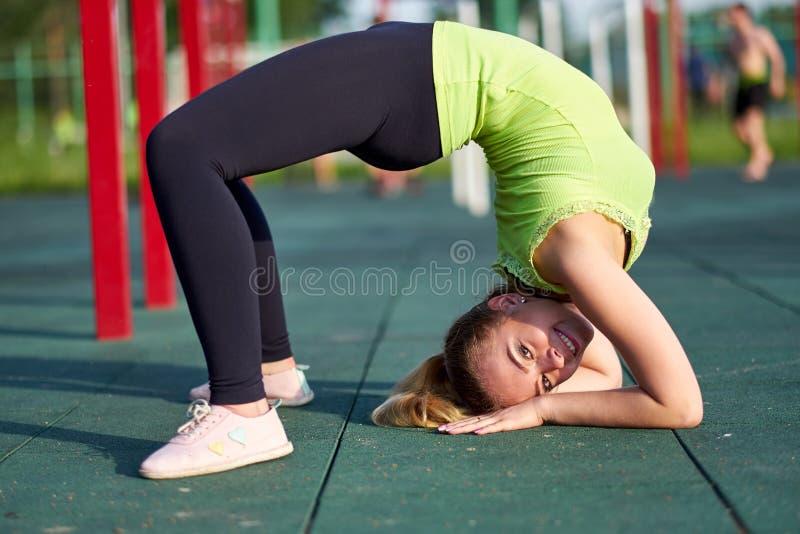 做锻炼桥梁的妇女 舒展danser或体操运动员训练在锻炼运动场训练 免版税库存照片