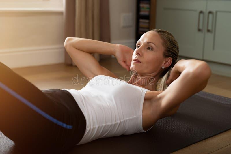 做锻炼的坚定的成熟妇女 免版税库存照片