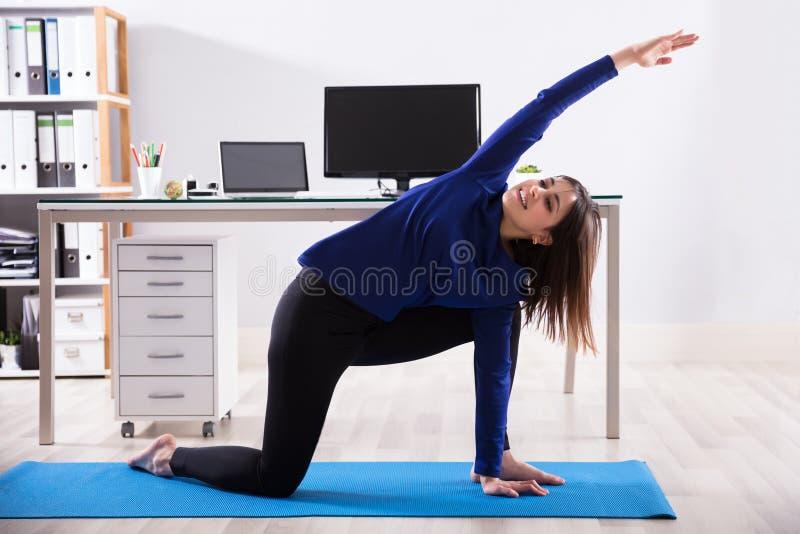 做锻炼的女实业家在办公室 图库摄影