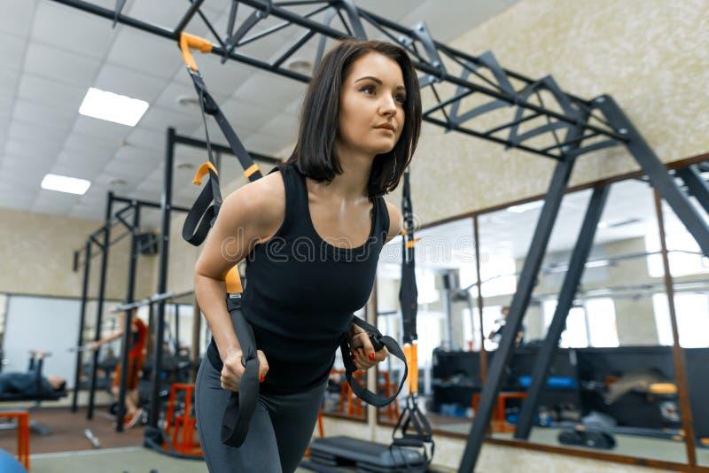 做锻炼的年轻健身妇女使用在健身房的trx系统 体育,健身,训练,人概念 免版税库存图片