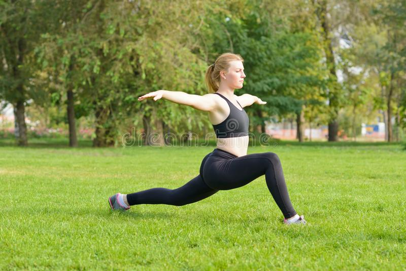 做锻炼的快乐的少妇在公园 库存图片