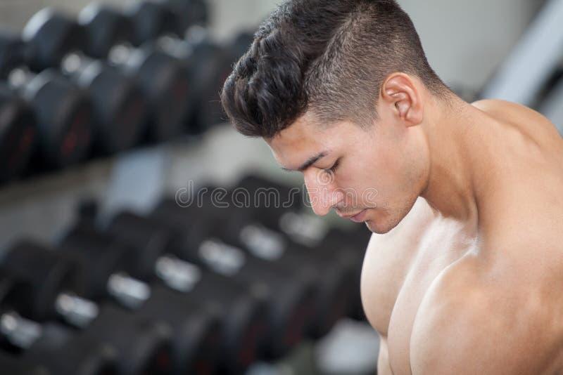 做锻炼的英俊的肌肉爱好健美者人的关闭坐与在健身房的举重哑铃 赤裸上身的体育年轻人 库存图片