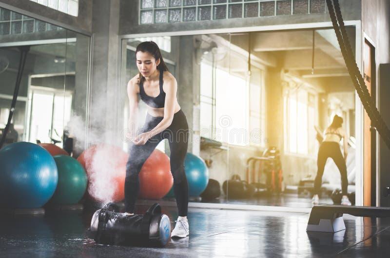 做锻炼训练的体育亚裔妇女,递举重运动员和尘土和肌肉在健身房 图库摄影