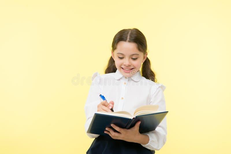 做附注 儿童做家庭作业的校服孩子 儿童女孩校服衣裳拿着书和笔 逗人喜爱的女孩 图库摄影