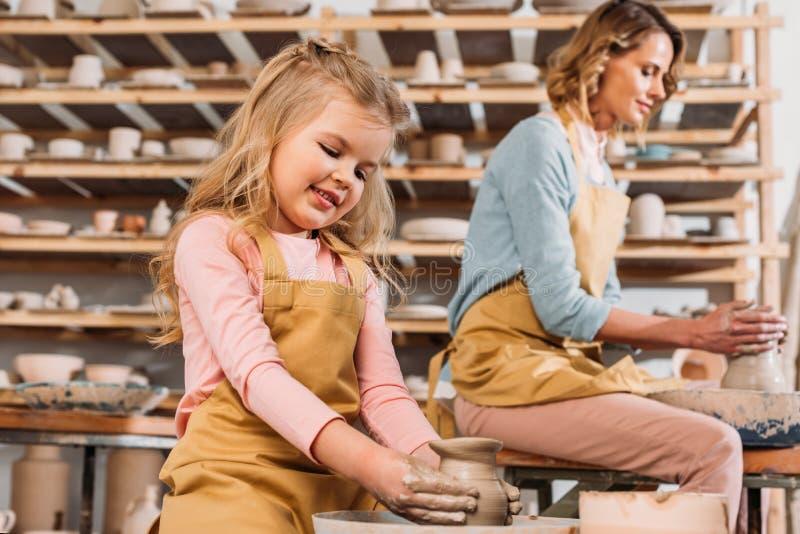 做陶瓷罐的妇女和孩子在瓦器轮子 图库摄影