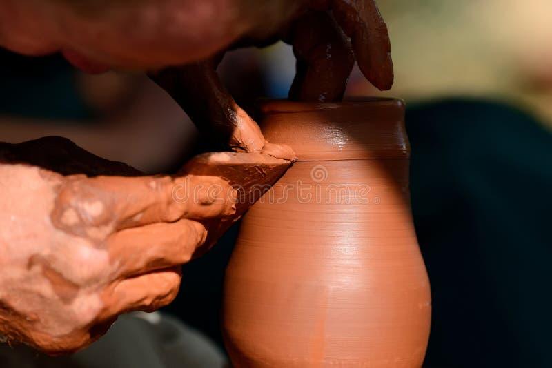 做陶瓷罐的陶瓷工在瓦器轮子 库存照片