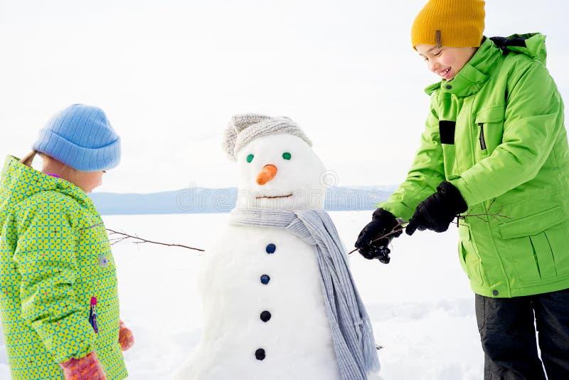 做雪人的孩子 免版税库存照片