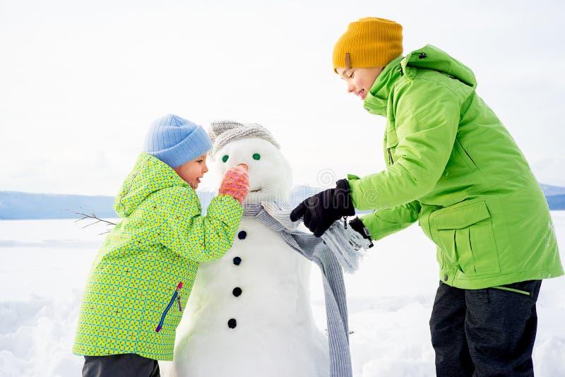 做雪人的孩子 免版税图库摄影