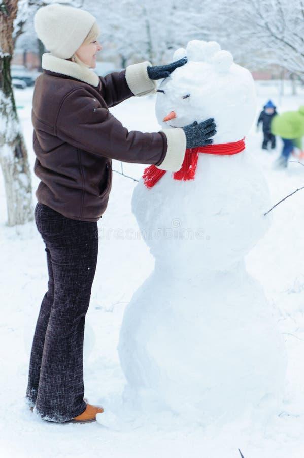 做雪人的美丽的妇女 库存图片