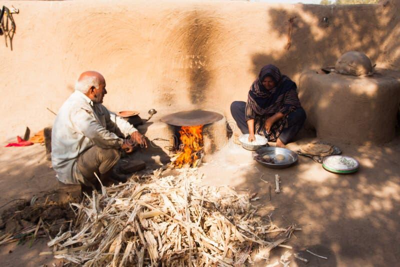 做面包的一名农村妇女,当她的丈夫做火时 免版税库存照片
