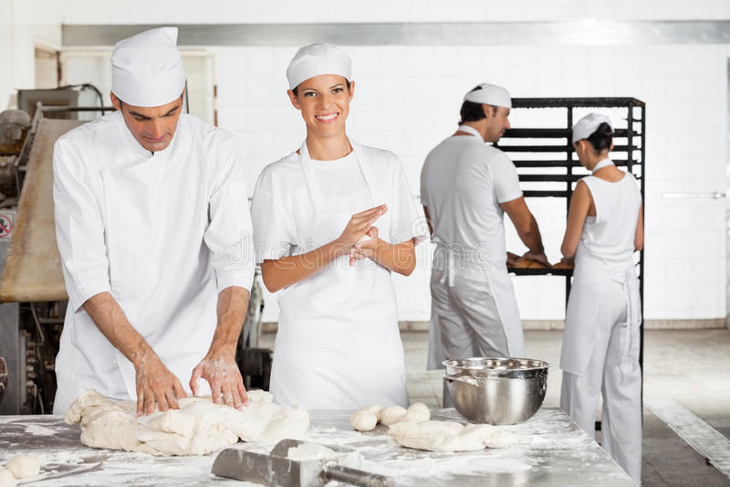 做面团球的贝克由男性同事在面包店 库存图片