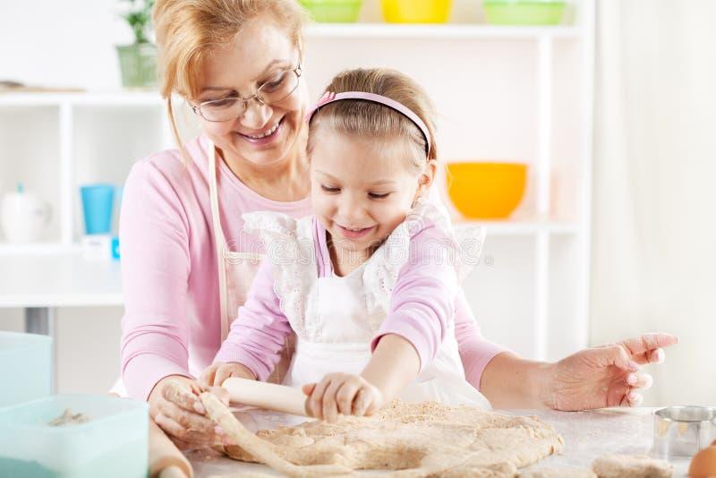 做面团的祖母和孙女 免版税库存照片
