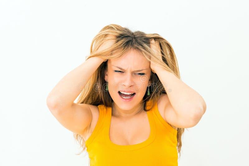 做面孔和拉扯头发的疯狂的妇女 免版税库存照片
