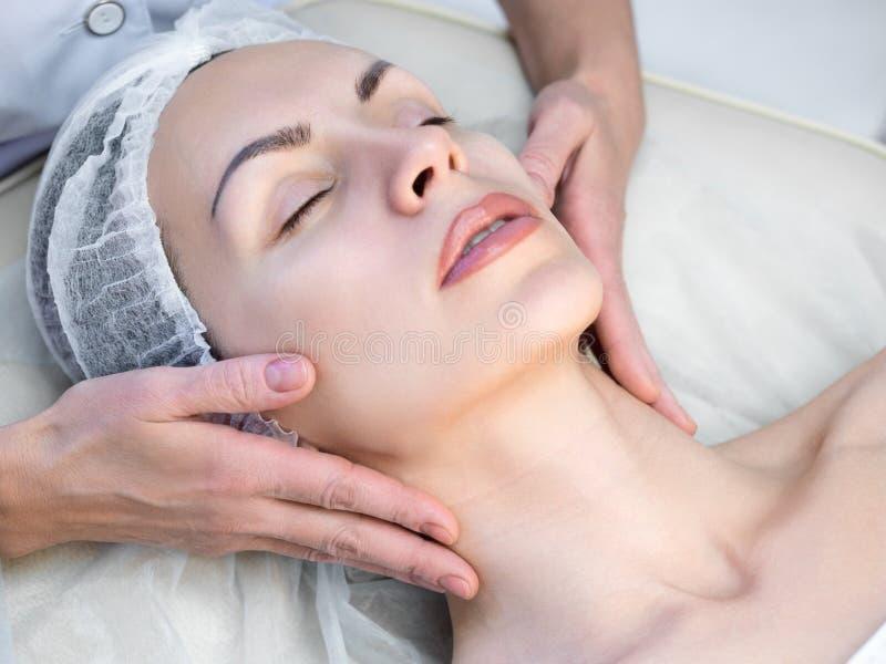 做面部按摩的美容师用人工在美容院里 在一次性盖帽的女性面孔有闭合的眼睛的 妇女放置 免版税库存照片