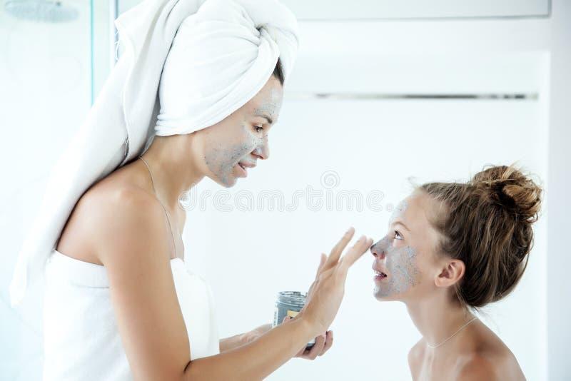 做面部面具的母亲和女儿 库存图片
