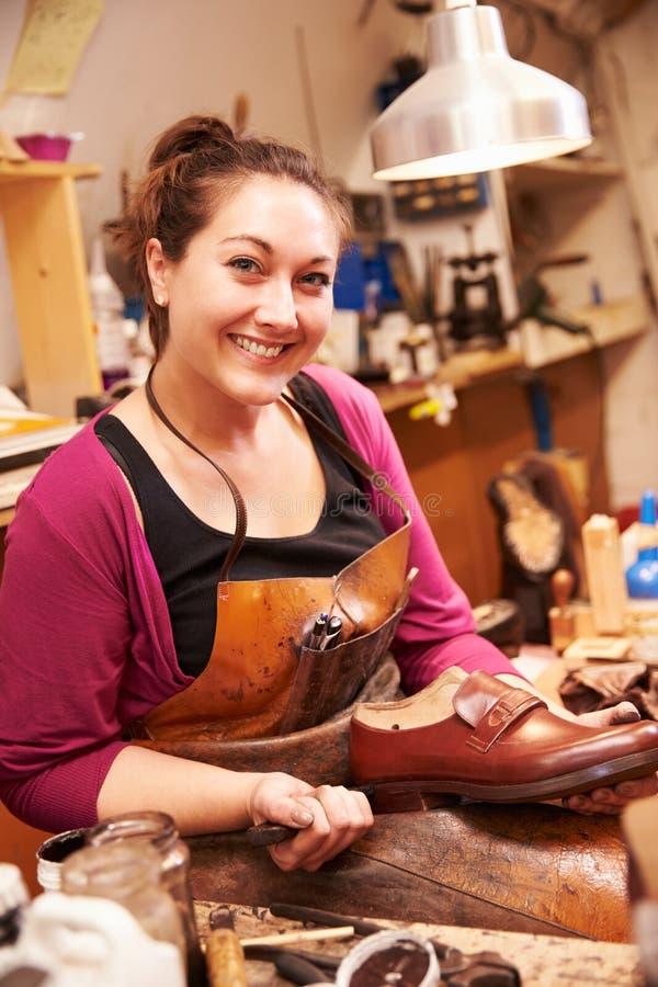 做鞋子的妇女鞋匠在车间 图库摄影