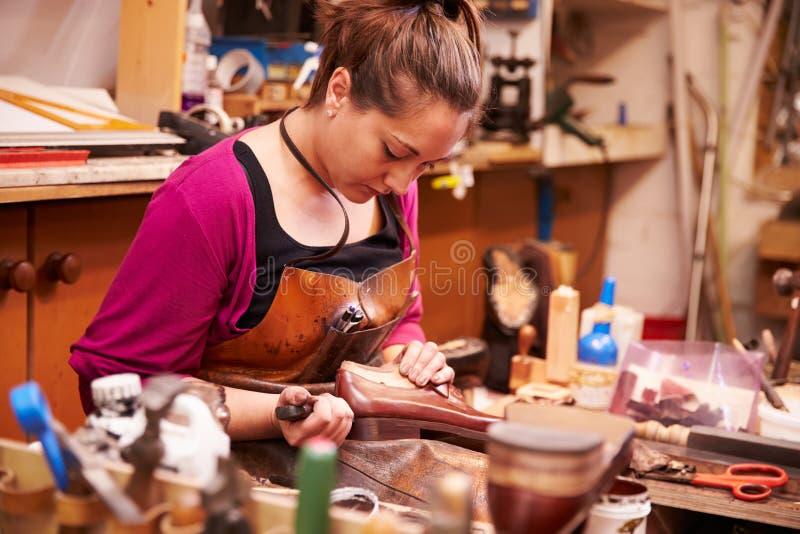 做鞋子的妇女鞋匠在车间 免版税库存图片