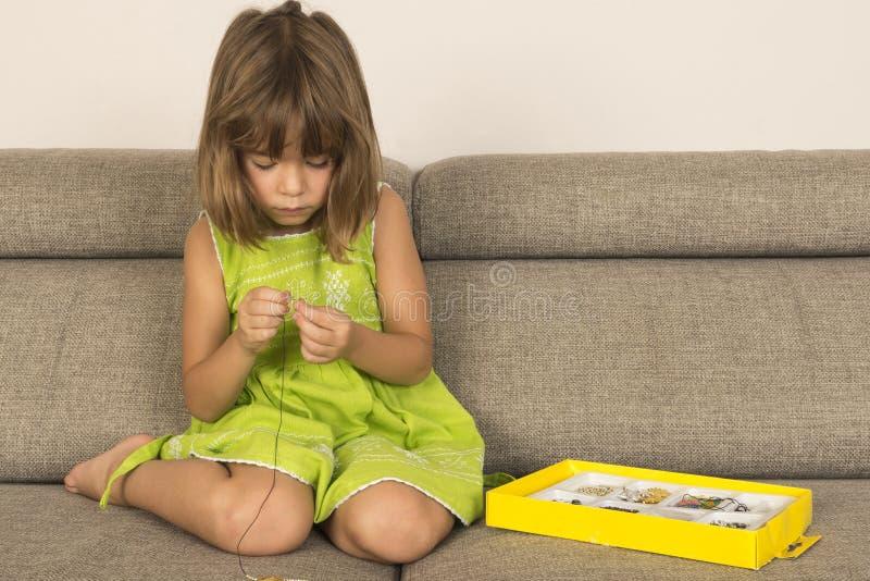 做项链的小女孩 免版税库存照片