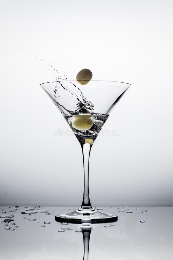 做飞溅的落的橄榄在马蒂尼鸡尾酒玻璃的伏特加酒 白色b 免版税库存照片