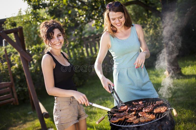 做食物的两个俏丽的女孩在格栅 免版税库存图片
