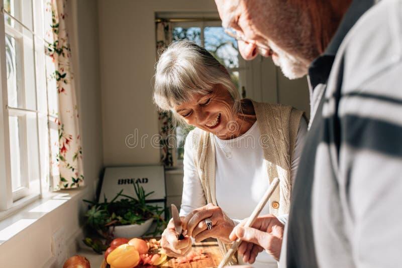 做食物的愉快的资深夫妇站立在厨房里 库存图片
