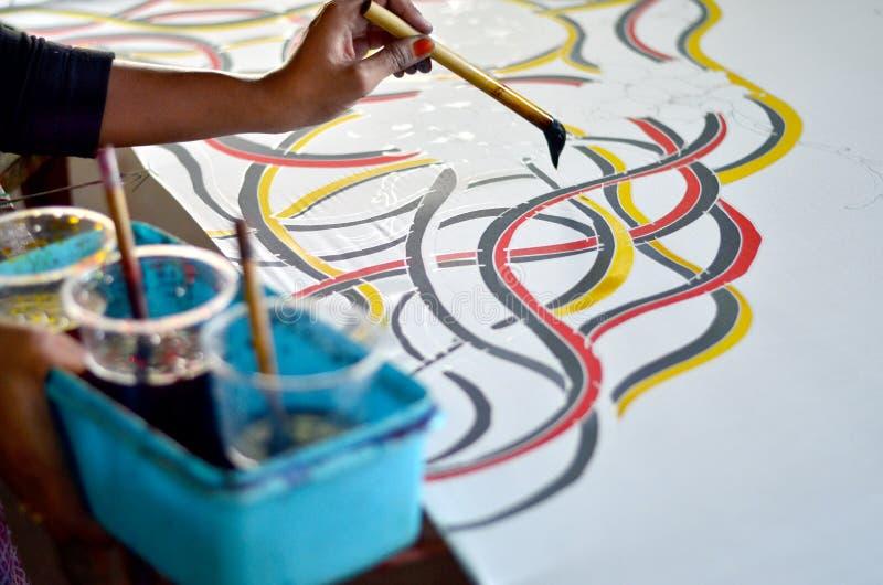 做马来西亚蜡染布的亚洲妇女手绘画 免版税库存图片