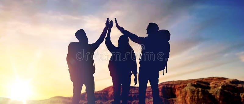 做高五在日出的旅行家 免版税库存照片