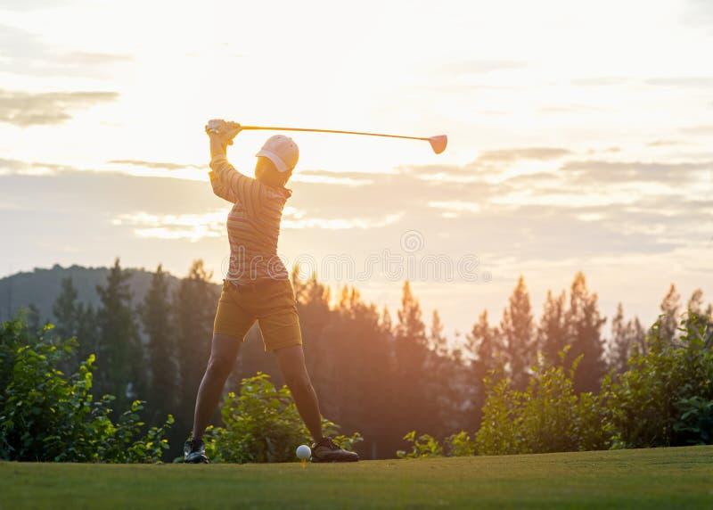 做高尔夫球摇摆发球区域在绿色日落晚上时间的亚裔女子高尔夫球运动员 免版税图库摄影