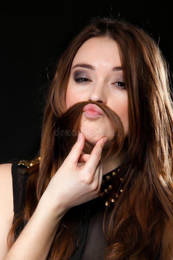 做鬼脸。女孩做傻的面孔的头发髭 库存图片