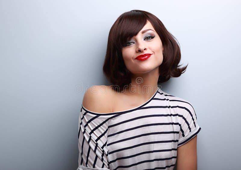 做鬼脸与短的黑发样式的滑稽的少妇 免版税库存照片