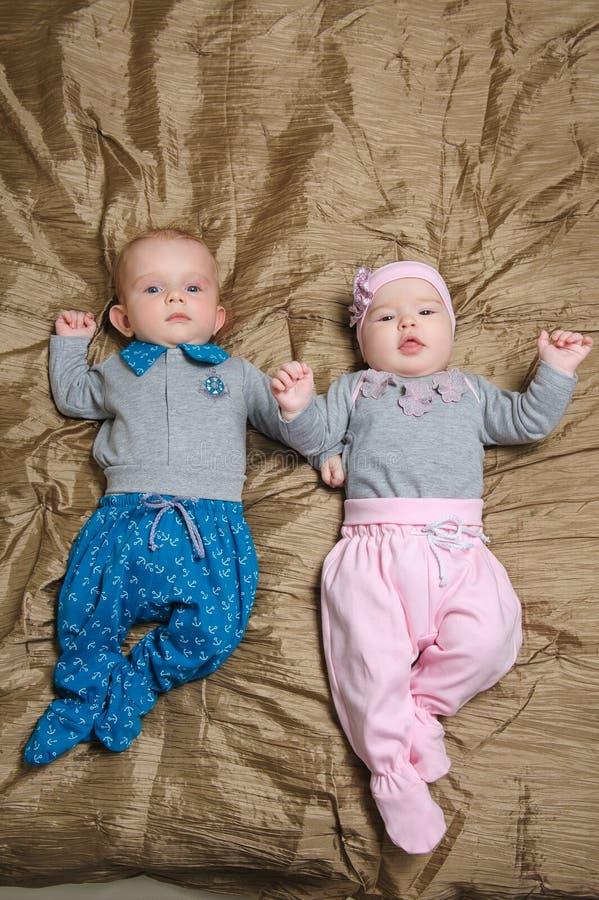 做鬼脸两个的婴孩说谎在坏和 图库摄影