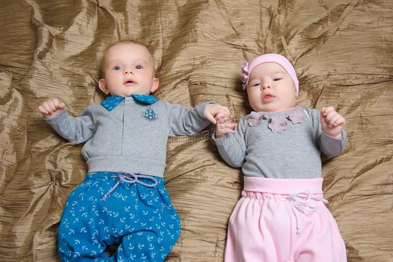 做鬼脸两个的婴孩说谎在坏和 免版税图库摄影