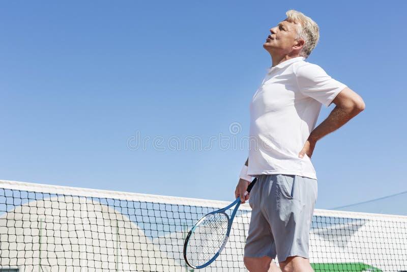 做鬼脸以腰疼的成熟人,当拿着网球拍反对清楚的天空蔚蓝在好日子时 免版税库存图片