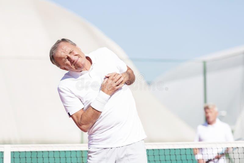 做鬼脸充满胸口痛的老人,当站立反对朋友在网球比赛期间在好日子时 免版税库存图片