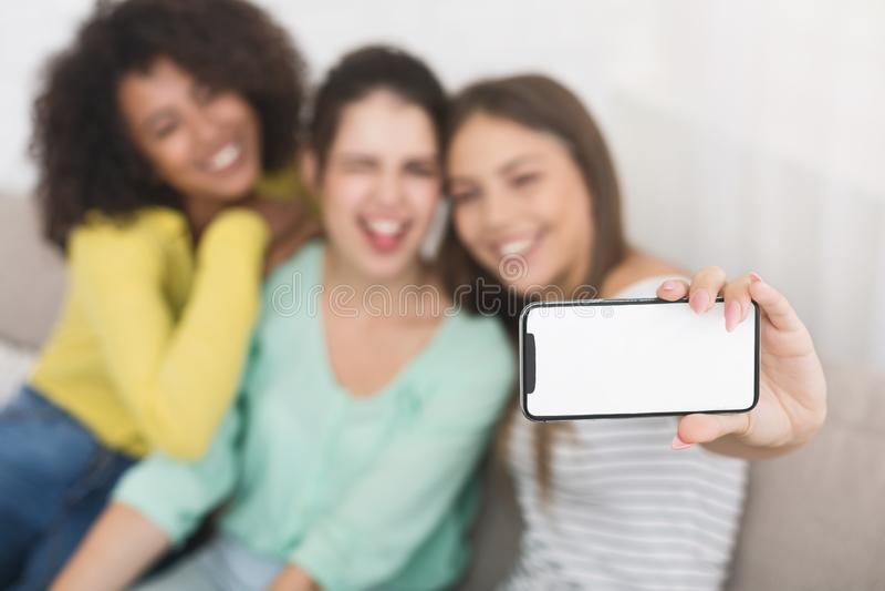 做鬼脸和做照片的朋友在智能手机 库存图片