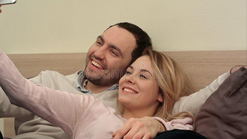 做鬼脸和采取selfie的愉快的夫妇在床 图库摄影