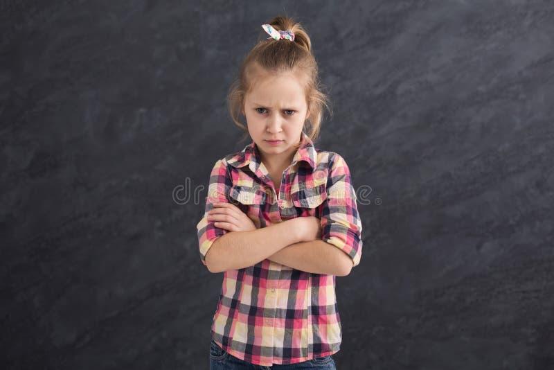 做鬼脸在灰色背景的小女孩 免版税图库摄影