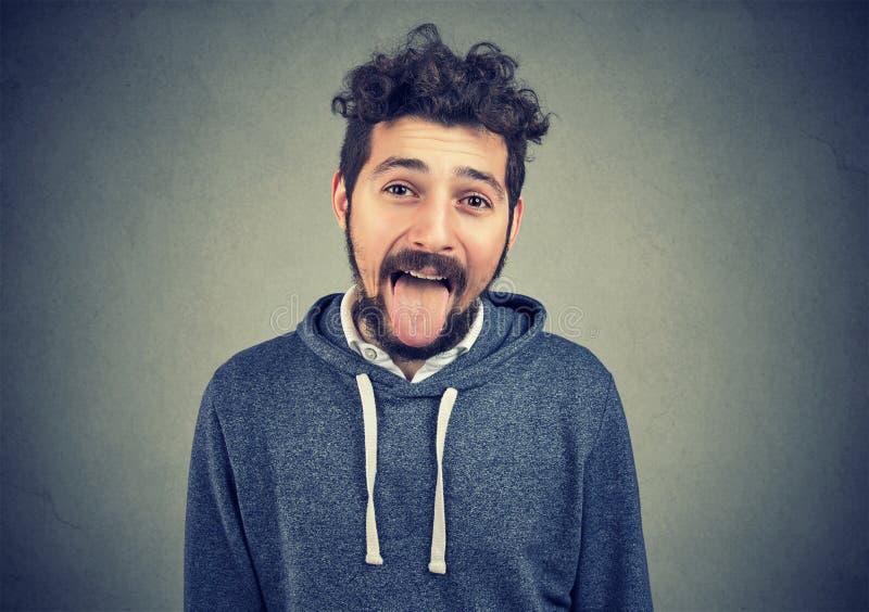 做鬼脸在照相机的幼稚人伸出他的舌头 免版税库存图片