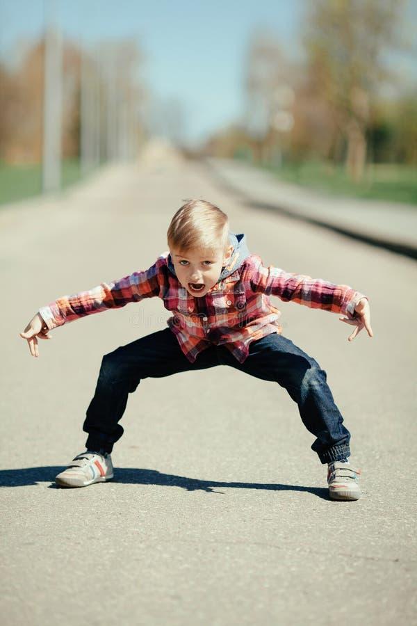 做鬼脸在街道上的小男孩 免版税库存照片