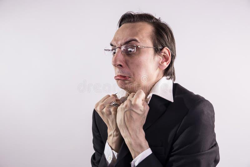 做鬼脸在他的工作场所的恼怒和frustraded商人 库存图片