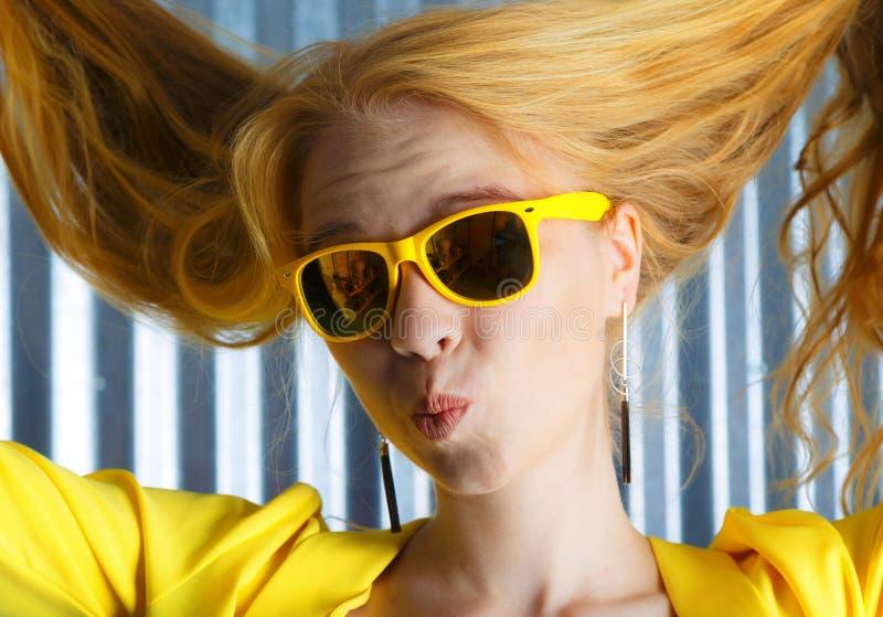 做鬼脸年轻白肤金发的妇女的关闭黄色太阳镜的 库存照片