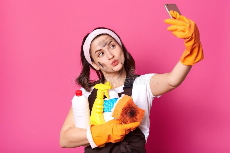 做鬼脸年轻的女服务生接近的射击做selfie和,保持嘴唇被环绕,拿着海绵,并且dertergents,展示 免版税图库摄影