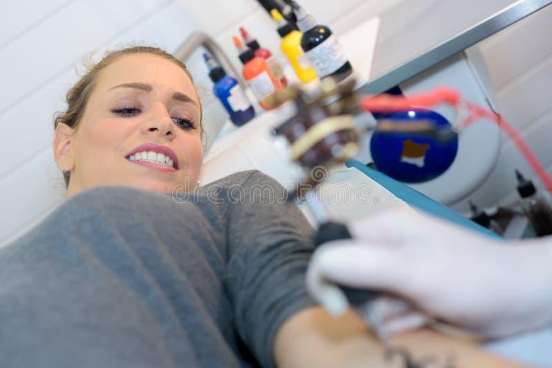 做鬼脸的妇女,当有纹身花刺时 免版税库存照片